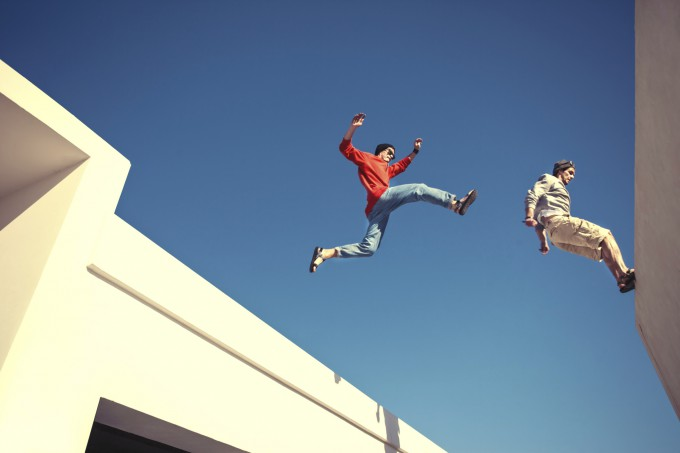 two brave men jumping over the roof